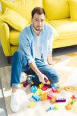 Fotografie Stilvolle junge Mann sitzt auf Teppich mit Kunststoffblöcke