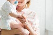 Bild der Mutter hält Tochter mit Baby-Dummy beschnitten