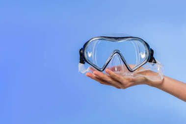 cropped view of female hand with swimming goggles, isolated on blue