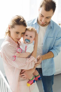 Mother holding infant daughter with baby dummy and father standing near