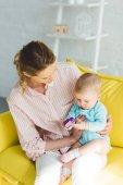 Fotografie Mutter und Tochter spielen mit Kunststoffblock
