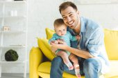 Young smiling father sitting on sofa with infant daughter in hands