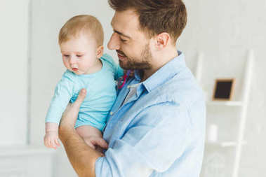 Smiling father holding infant daughter in hands