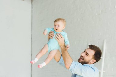 Smiling father raising infant daughter in air