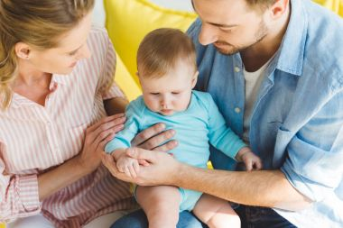 Young parents holding infant daughter in hands