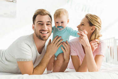 Happy young family and infant daughter with baby dummy