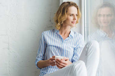 Stylish young woman looking in window and holding cup of coffee