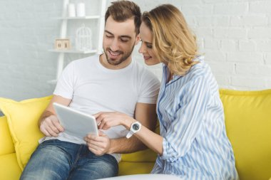 Smiling couple having fun with tablet and sitting on sofa
