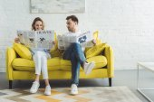 Fotografie Businessman with wife reading newspapers about travel and business while sitting on sofa in modern room with painting