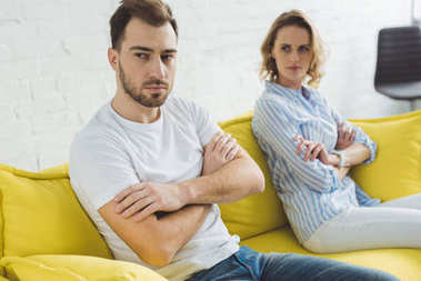 Young upset couple sitting on couch after argue