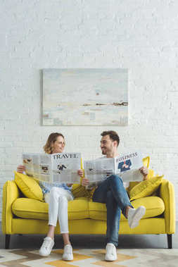 Stylish businessman with girlfriend reading newspapers about business and travel