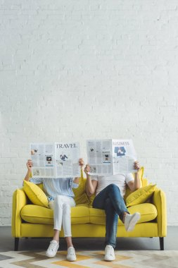 Businessman with girlfriend sitting on sofa and reading newspapers about travel and business