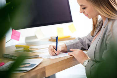 side view of female marketing manager doing paperwork at workplace in office