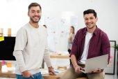 szelektív összpontosít a mosolygó marketing menedzserek, munkahely, iroda támaszkodva laptop