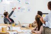 podnikatel, ukázala na bílou tabuli s doklady během setkání s multikulturní kolegy v kanceláři
