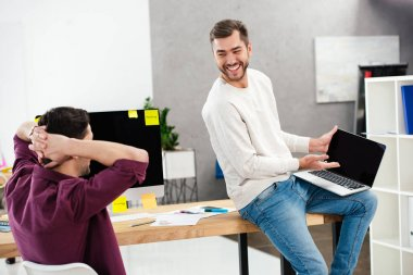 cheerful businessmen working with laptop at workplace together in office
