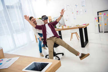 cheerful businessman in vr headset with colleague near by in office