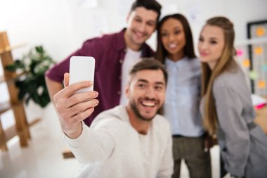 Selective focus of happy multicultural business people taking selfie on smartphone together in office stock vector