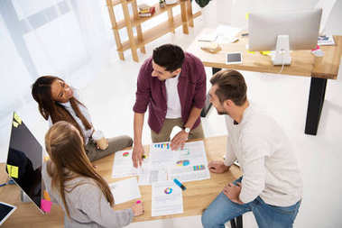Overhead view of multiethnic business colleagues discussing new marketing project at workplace in office stock vector