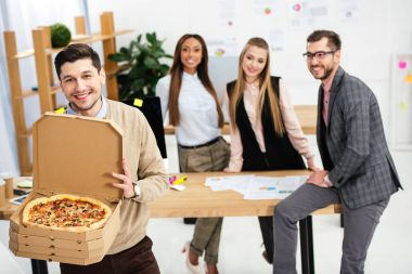 selective focus of smiling businessman with pizza in hands and multiethnic colleagues behind in office