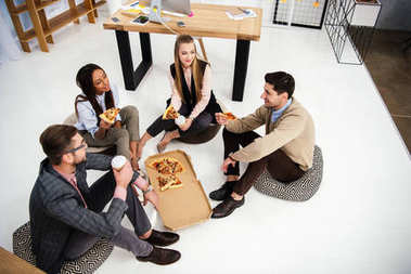 high angle view of multiethnic business people eating pizza in office