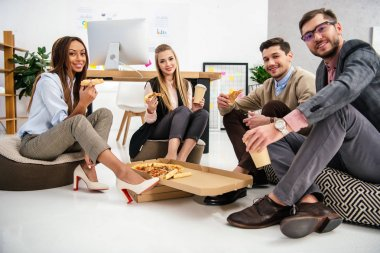 smiling multiethnic business people with pizza looking at camera in office