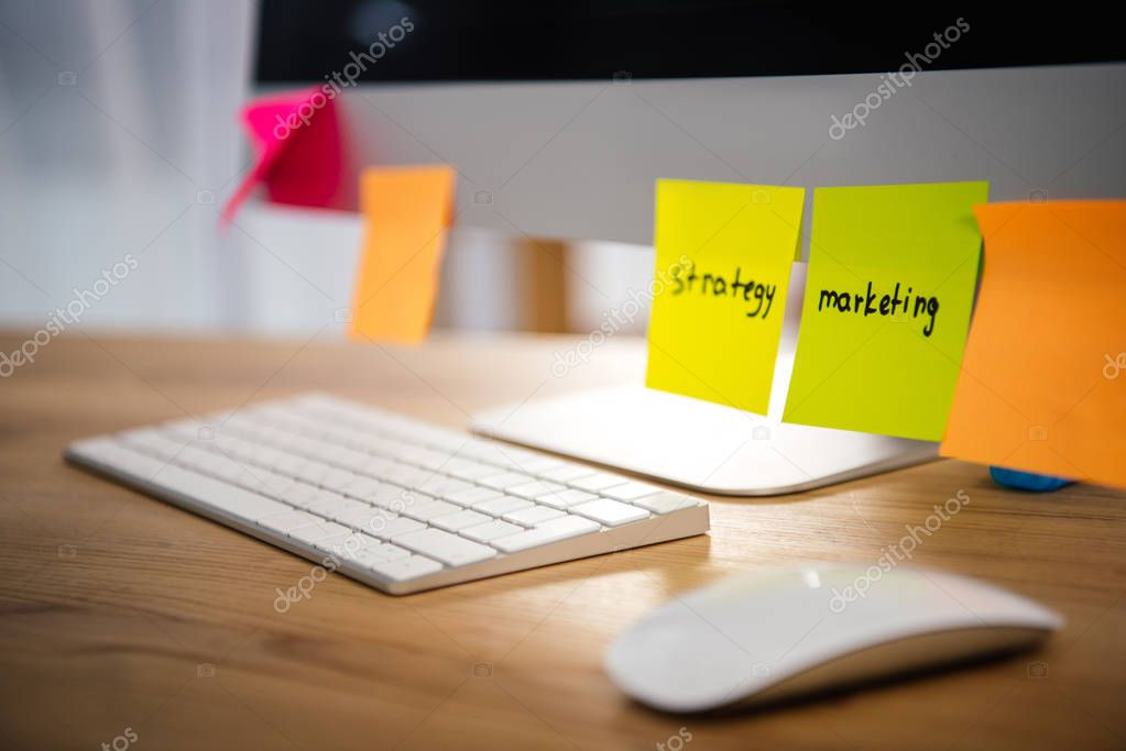 close up view of colorful sticky notes with marketing and strategy lettering on computer screen at workplace