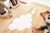 Fotografie partial view of multiracial business people at wooden table with empty paper clouds, teamwork concept