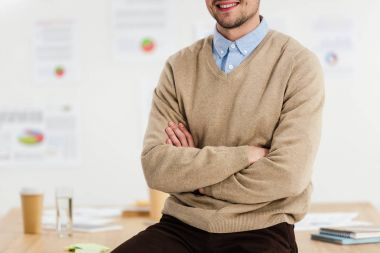 partial view of smiling marketing manager with arms crossed leaning on workplace in office