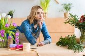 pensive young florist leaning at table and looking away in flower shop
