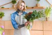 vonzó fiatal tetovált nő kötény gazdaság gyönyörű csokor virág bolt