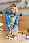 beautiful young female florist in apron looking at camera while working in flower shop