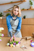 Fotografie beautiful young female florist in apron looking at camera while working in flower shop