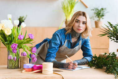 young florist taking notes and looking at camera at workplace