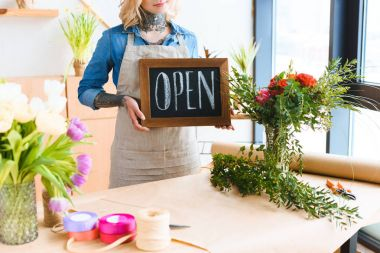 cropped shot of young florist holding open sign in flower shop