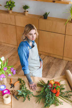 high angle view of beautiful young florist in apron standing at workplace