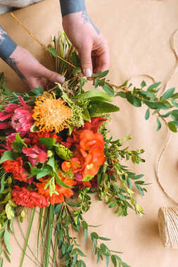 close-up partial view of woman arranging beautiful flowers into bouquet