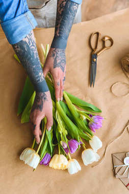 cropped shot of florist with tattoos arranging beautiful tulips at workplace