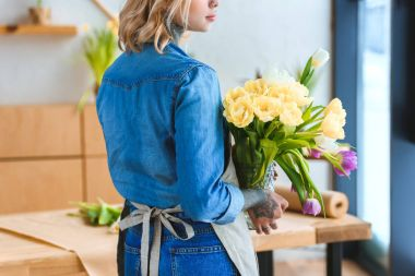 back view of young florist holding beautiful tulips in vase