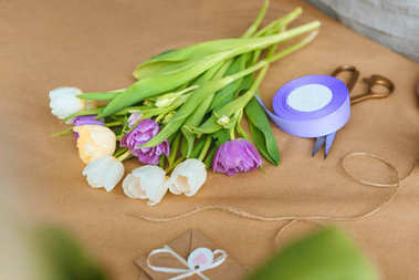 close-up view of beautiful tender tulips, rope, ribbon and scissors on craft paper