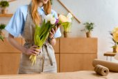 Photo cropped shot of florist in apron holding beautiful tulips at workplace