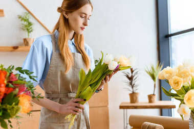young florist in apron holding beautiful tulips in flower shop