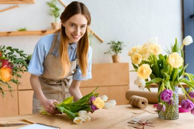 beautiful young florist wrapping tulips in craft paper and smiling at camera