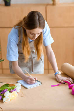 young female florist taking notes in notebook at workplace