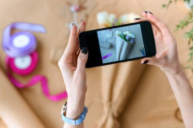 cropped shot of woman holding smartphone and photographing beautiful bouquet of tulips in craft paper