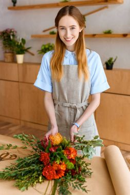 beautiful young florist arranging flower bouquet and smiling at camera
