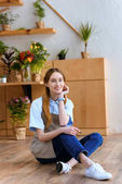Fotografie schöne junge Frau in Schürze am Boden und lächelt in die Kamera im Blumenladen
