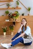 Fotografie schöne junge Floristen am Boden und lächelt in die Kamera im Blumenladen