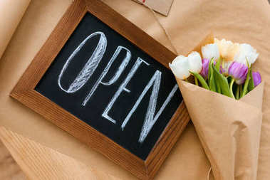 top view of beautiful bouquet of tulips and open sign on craft paper