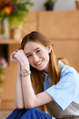 portrait of beautiful young female florist smiling at camera